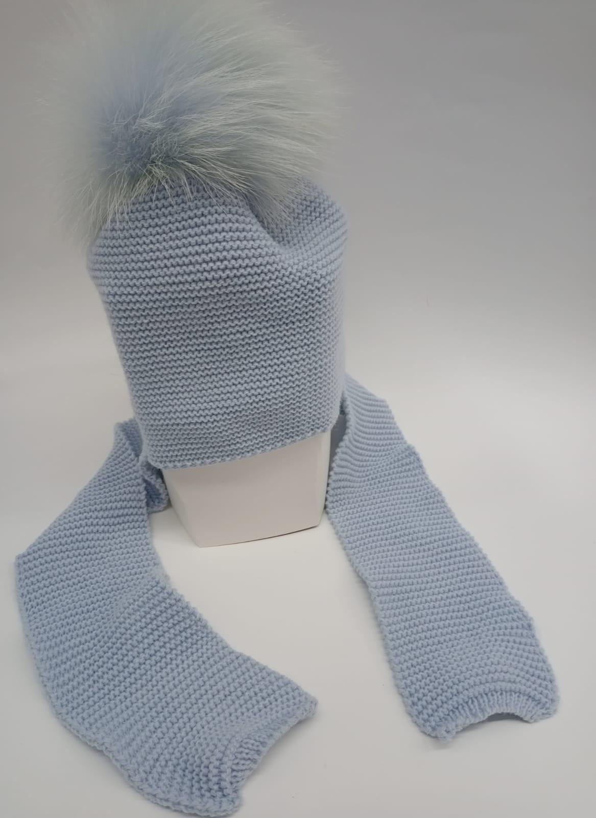 Gorro con bufanda unida en azul empolvado y pompón de pelo