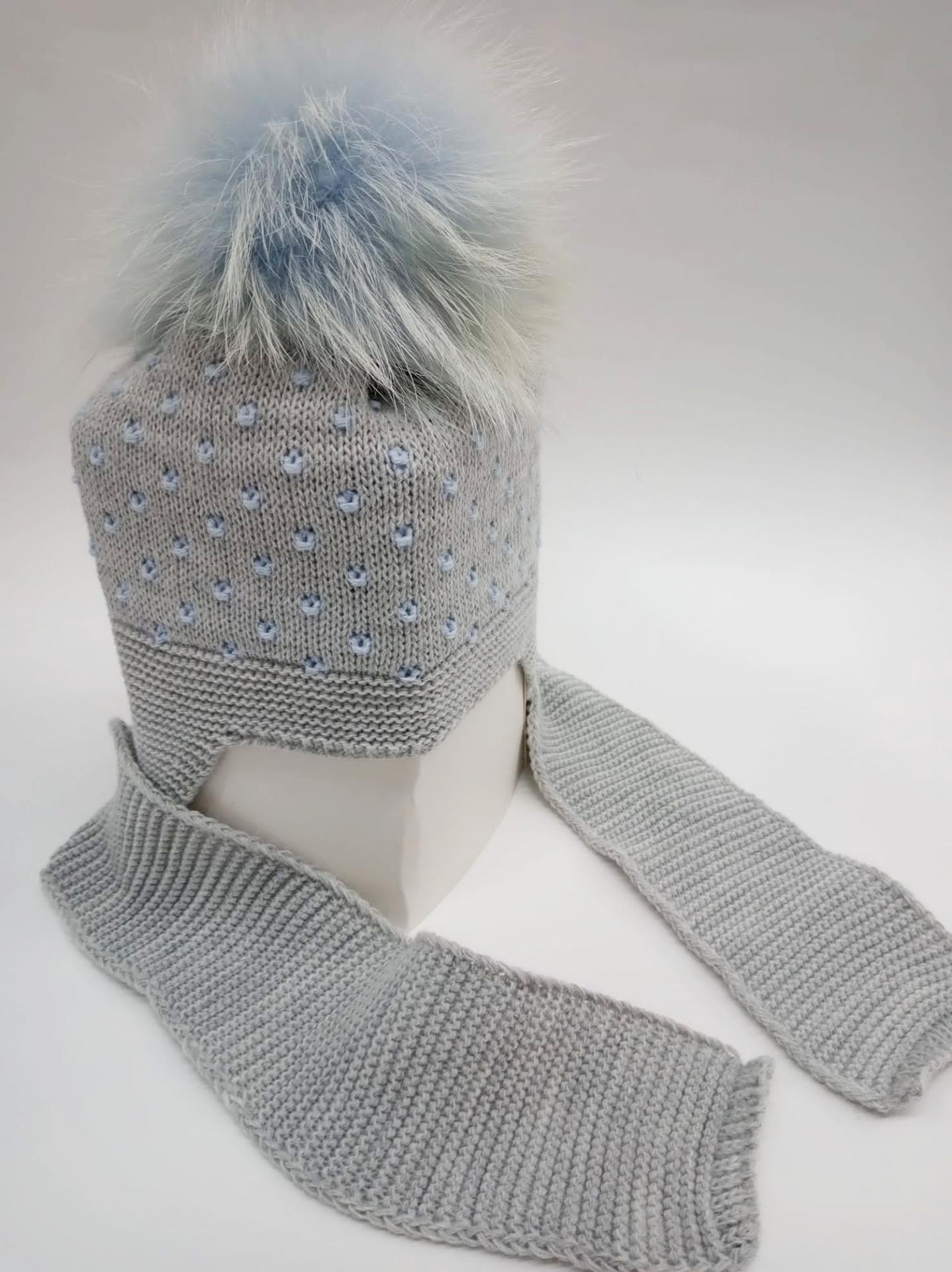 Gorro gris con motas azules con bufanda unida y pompóm de pelo natural.