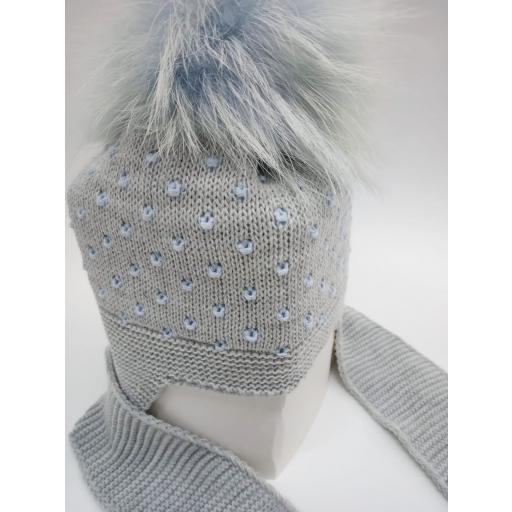 Gorro gris con motas azules con bufanda unida y pompóm de pelo natural. [1]