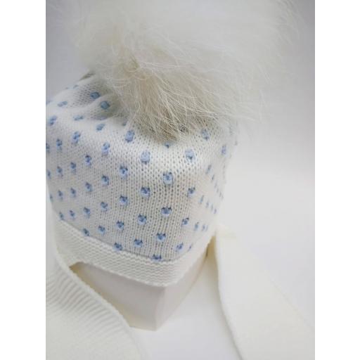 Gorro marfil con motas azules, con bufanda unida y pompóm de pelo natural. [1]