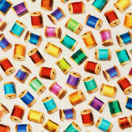 Tela patchwork de fondo beige con carretes de hilos