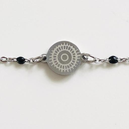 Pulsera de acero plateado con bolitas negras y círculo grabado