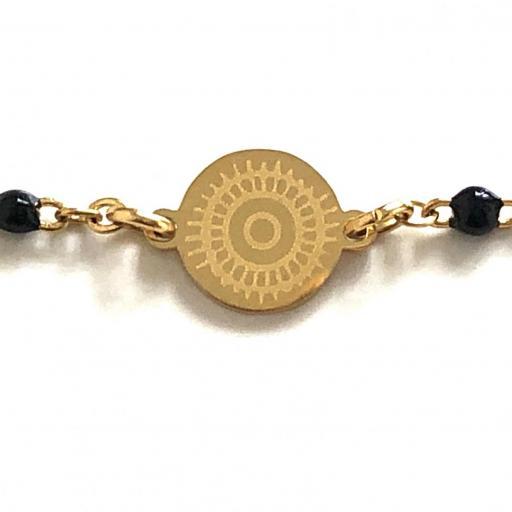 Pulsera de acero dorado con bolitas negras y círculo grabado