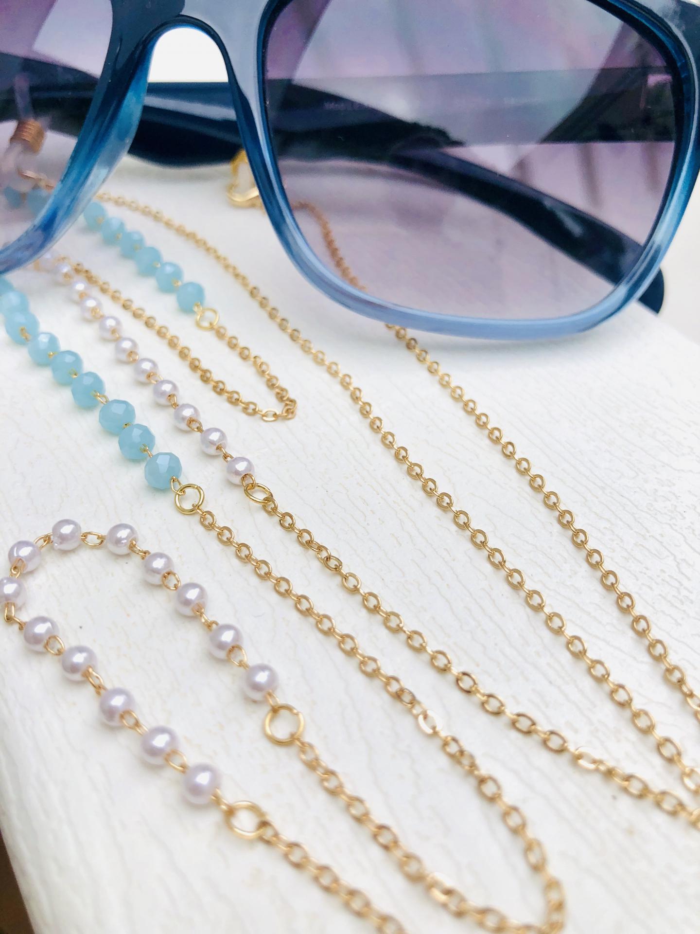Cadena gafas de acero dorado, bolitas de strass color celeste y perlas blancas
