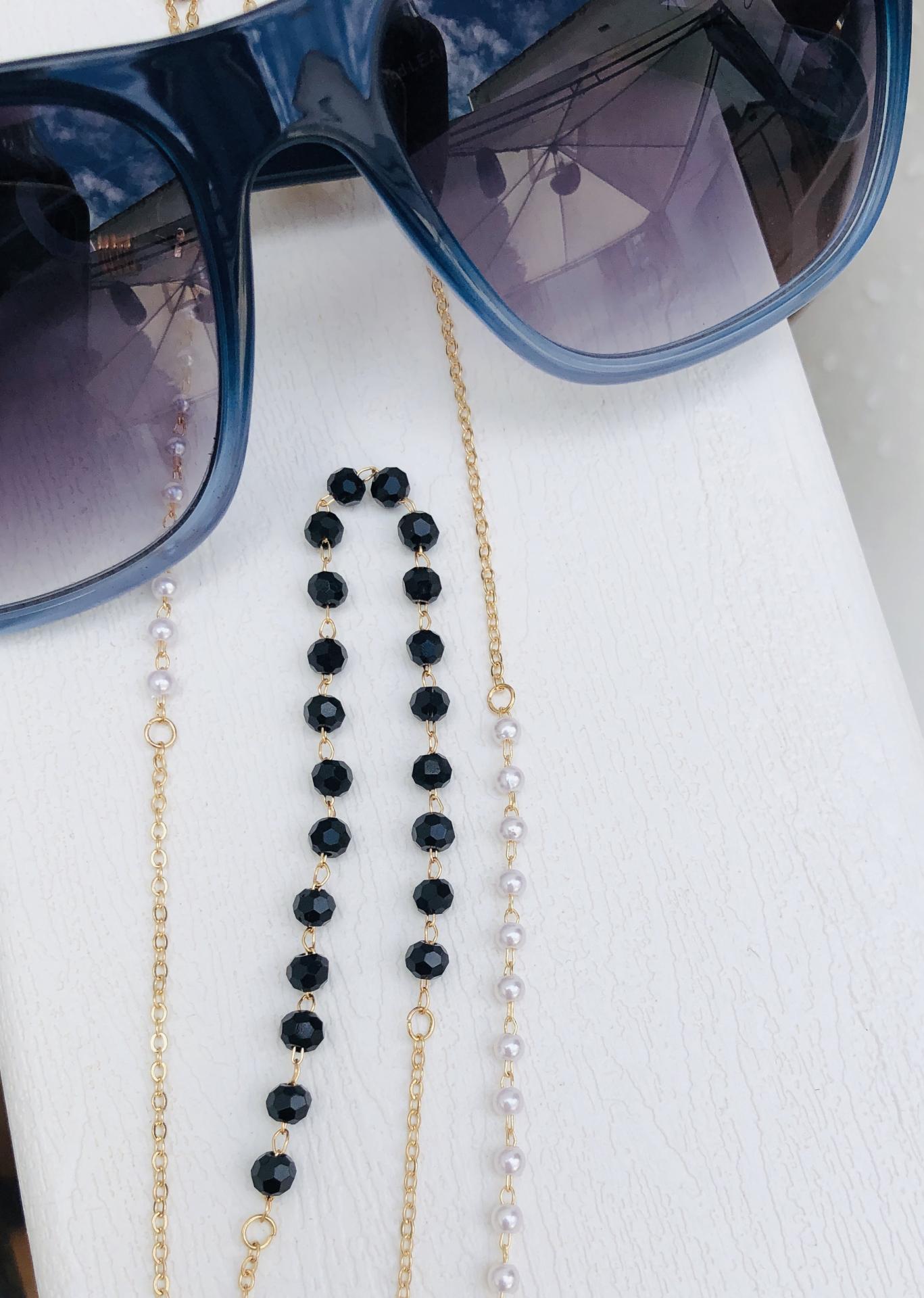 Cadena gafas de acero dorado, bolitas de strass color negro y perlas blancas