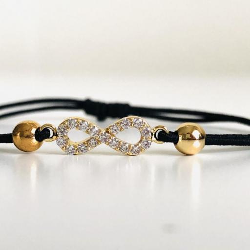 Pulsera de hilo elástico negro con infinito dorado y cristales