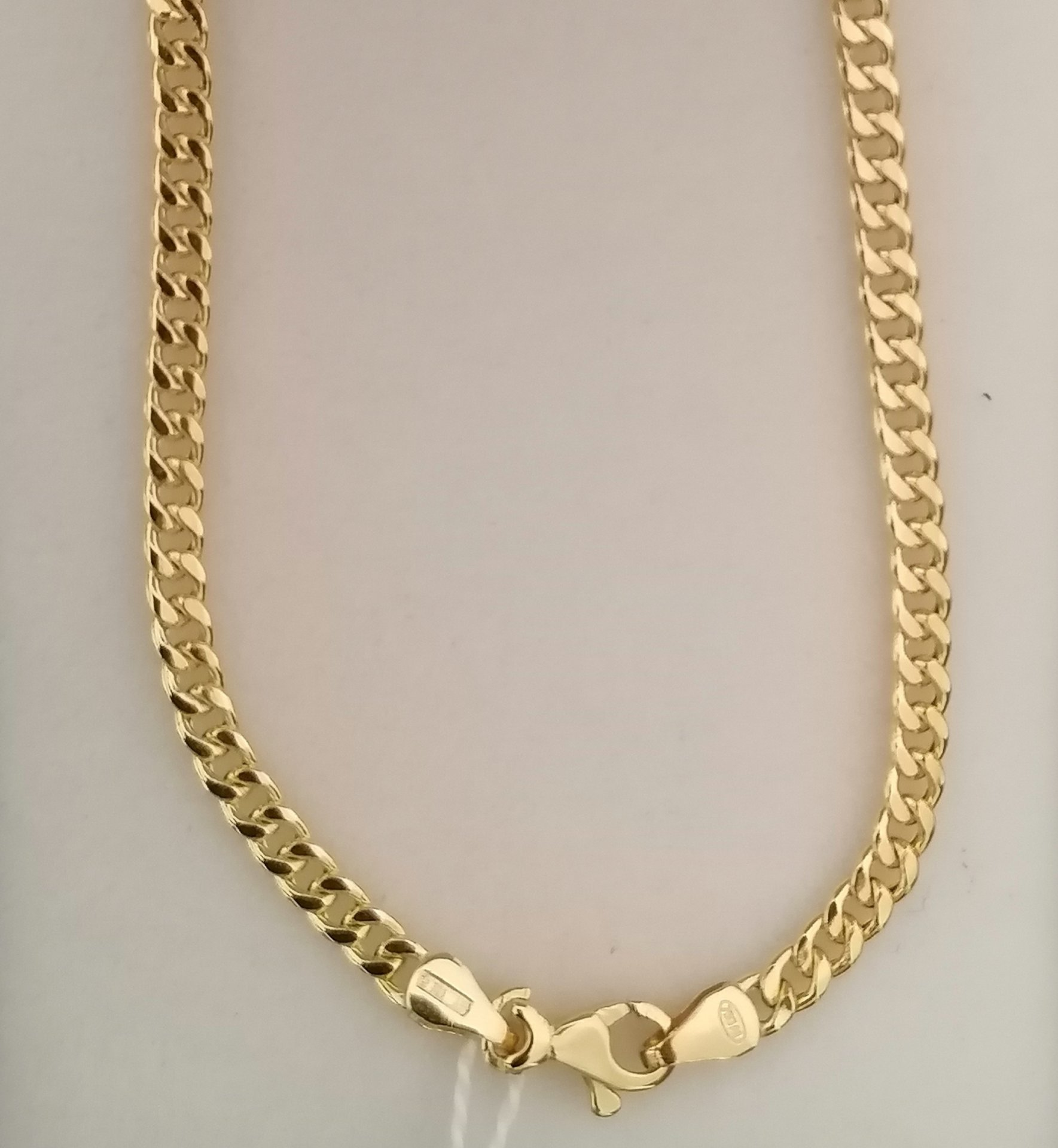 Esta cadena barbada de oro incorpora broche de mosqueton y contraste